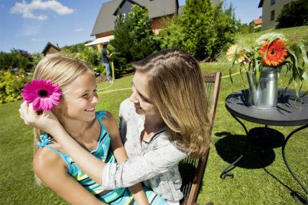 Tochter mit Mutter im Garten, steckt Blume ins Haar